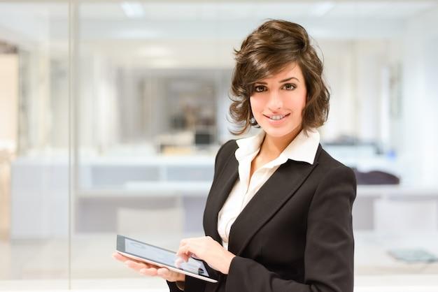 Trabajadora sonriente con la tableta en la oficina
