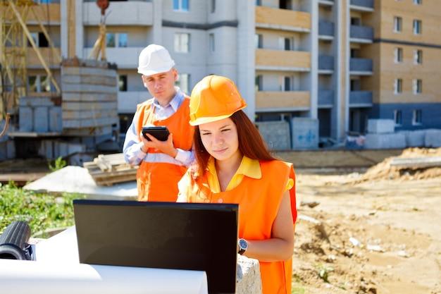 Trabajadora y trabajador de la construcción mirando portátil juntos contra la construcción