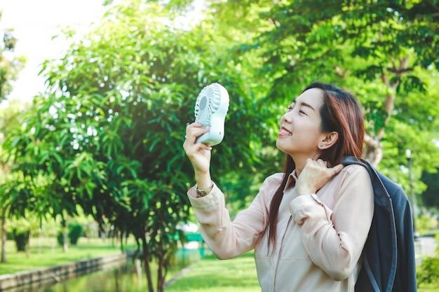 Las trabajadoras asiáticas se quitan las camisas de su traje debido al clima extremadamente caluroso. use un pequeño ventilador para ayudar a reducir el calor.