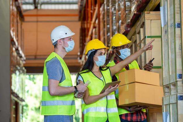 Los trabajadores del almacén grupal que usan una máscara protectora trabajando juntos en el almacén, coronavirus se ha convertido en una emergencia global.