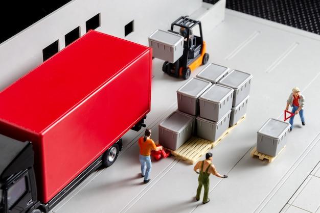 Trabajadores de almacén en miniatura montacargas que transportan caja de mercancías a semi camión con remolque