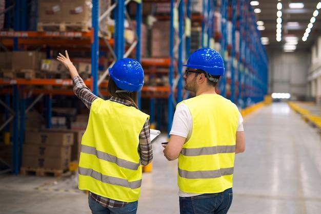 Trabajadores del almacén que comparten ideas para una mejor organización y eficiencia