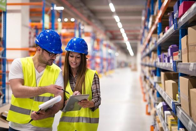 Trabajadores del almacén que controlan el inventario y se consultan entre sí sobre la organización y distribución de mercancías.