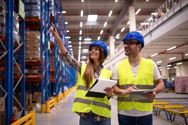 Trabajadores del almacén en uniforme de protección caminando por un gran centro de distribución organizando la distribución de mercancías