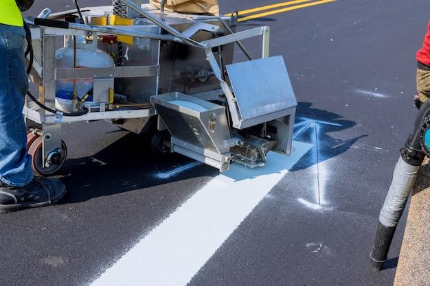 Los trabajadores aplican pintura blanca a una carretera que marca las rayas con un polvo reflectante sobre el nuevo asfalto