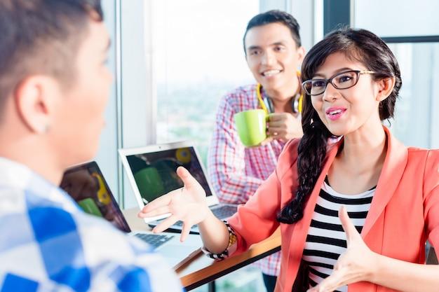 Trabajadores asiáticos de la agencia creativa discutiendo