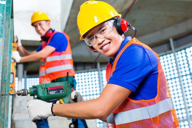 Trabajadores asiáticos de la construcción que perforan en las paredes del edificio