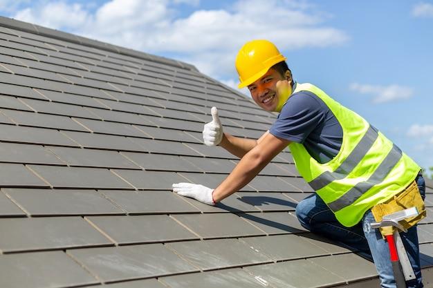 Los trabajadores asiáticos de techado de tejas levantaron los pulgares para indicar la estabilidad del techo.