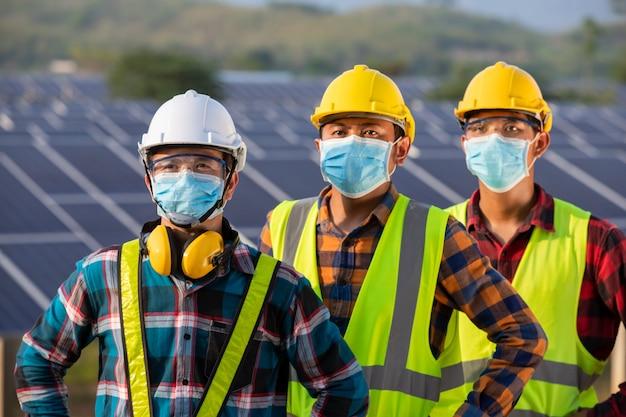 Los trabajadores asiáticos usan máscaras protectoras para seguridad en el sitio de construcción electricidad industria de energía solar, energía natural, nueva normalidad