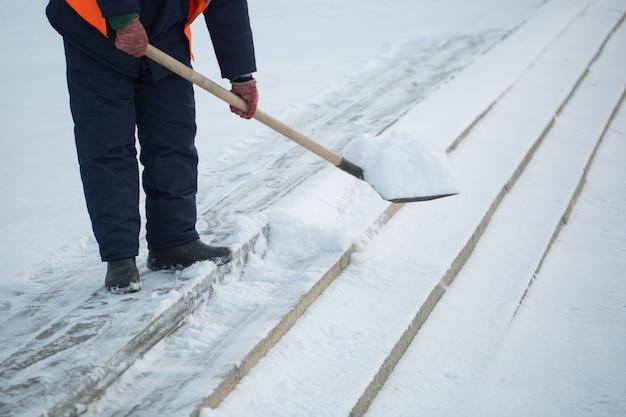Los trabajadores barren la nieve de la carretera en invierno