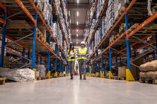 Trabajadores con cascos y chaquetas reflectantes caminando por el gran pasillo del almacén comprobando el estado de las mercancías