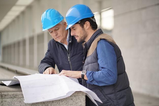 Trabajadores en cascos que consultan sobre planos en vista de edificio moderno