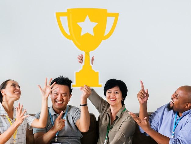 Trabajadores celebrando su éxito con un trofeo