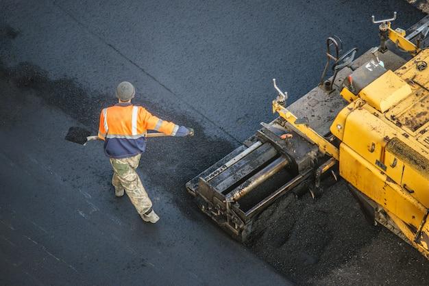 Los trabajadores colocan una nueva capa de asfalto con betún caliente. trabajo de maquinaria pesada y pavimentadora. vista superior