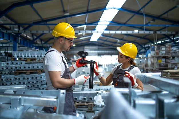 Trabajadores comprobando piezas fabricadas en fábrica.