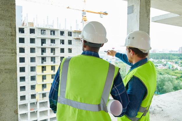 Trabajadores de constricción discutiendo la estructura del edificio
