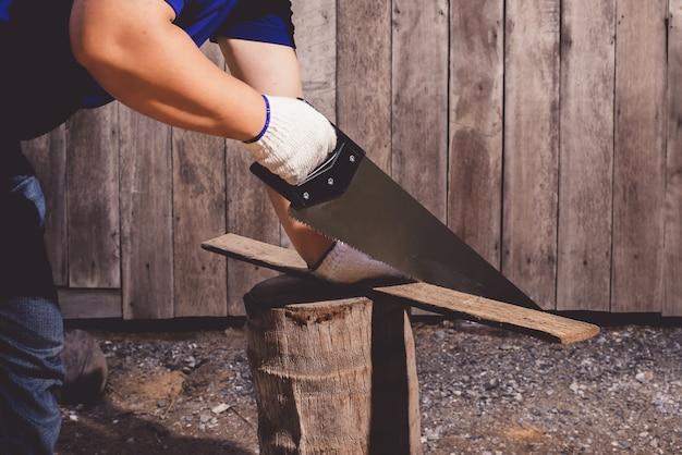 Trabajadores de la construcción en camisa azul con guantes protectores trabajando con sierra