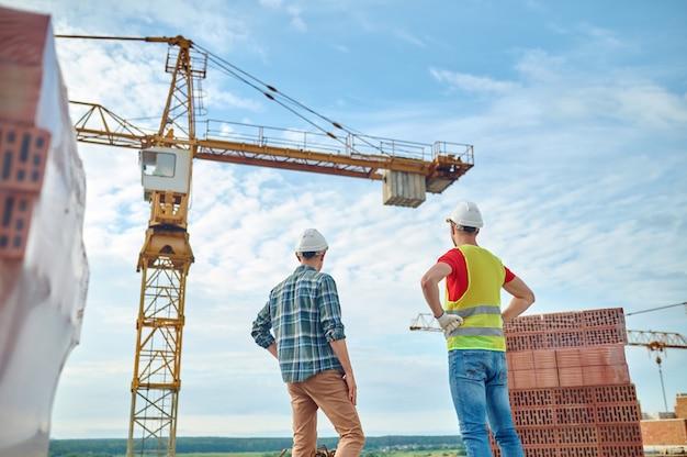 Trabajadores de la construcción experimentados en cascos comprobando el sitio de construcción