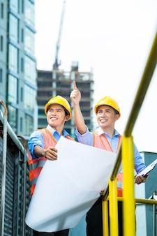 Trabajadores de la construcción indonesios asiáticos con plano o plan en el sitio de construcción