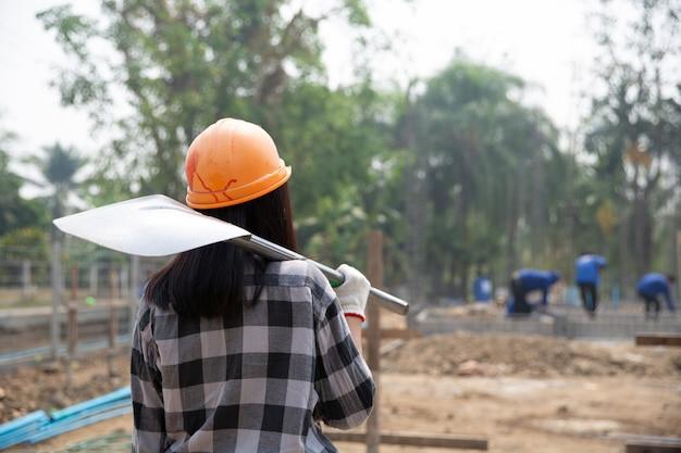Trabajadores de la construcción llevando una pala al sitio de construcción