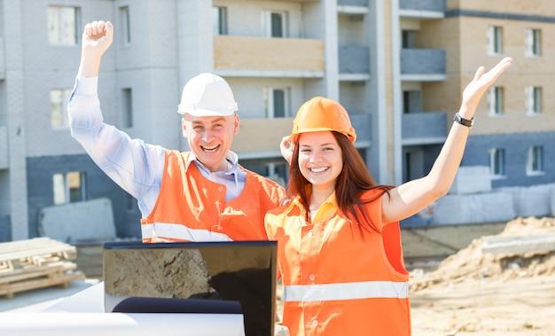 Trabajadores de la construcción masculinos y femeninos de éxito mirando portátil