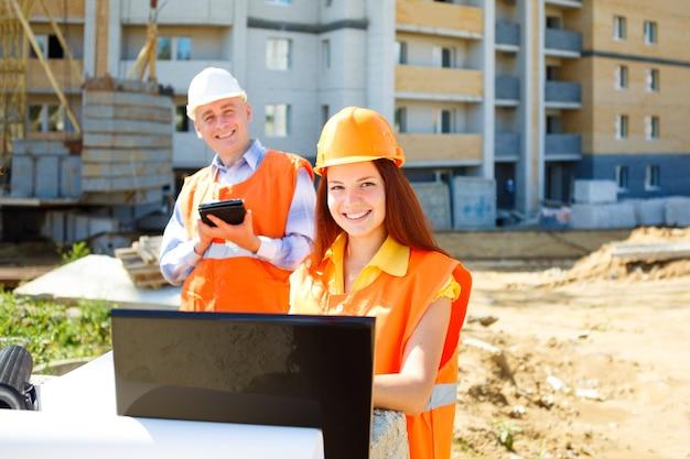 Trabajadores de la construcción masculinos y femeninos mirando portátil y sonriendo