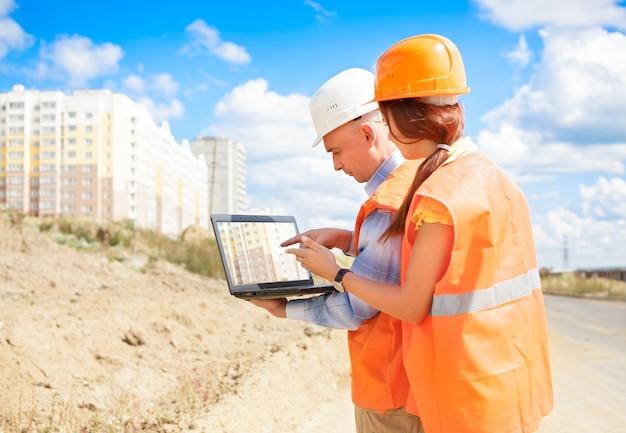 Trabajadores de la construcción masculinos y femeninos mirando portátil