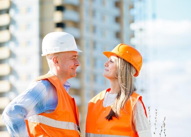 Trabajadores de la construcción masculinos y femeninos mirar hacia arriba