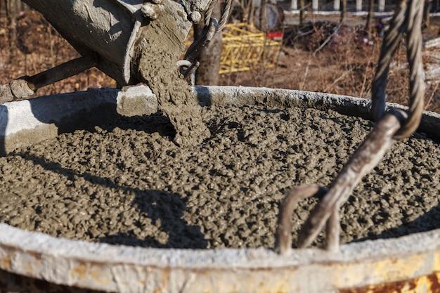 Trabajadores de la construcción que vierten el concreto mojado usando el cubo concreto