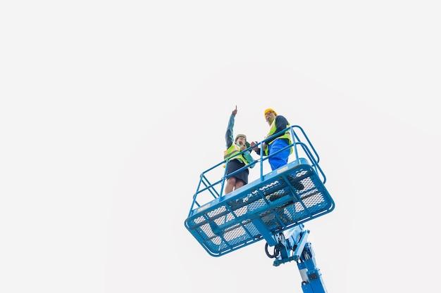 Trabajadores de la construcción en el sitio en la rampa de elevación hidráulica discutiendo el proyecto en la plataforma o tableta
