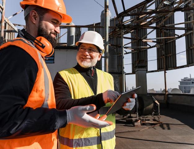 Trabajadores de la construcción de tiro medio con tableta