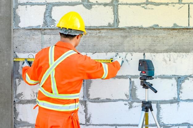 Trabajadores de la construcción está utilizando un medidor de nivel láser para dispositivos de nivelación de pared
