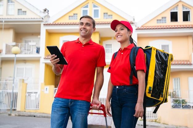 Trabajadores de correos sonrientes de pie y buscando la dirección de la casa en la tableta. dos mensajeros felices entregando el pedido en bolsa térmica y vistiendo camisetas rojas. servicio de entrega y concepto de compra online.