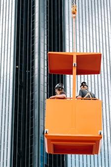 Los trabajadores en una cuna de construcción se suben a una grúa a un gran edificio de vidrio. la grúa levanta a los trabajadores en el asiento del automóvil.
