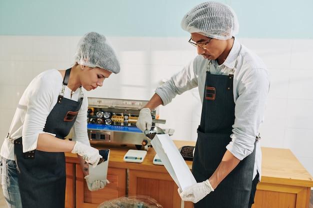 Trabajadores empacando granos de café tostado en paquetes de papel