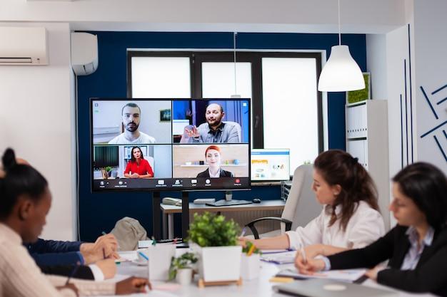 Trabajadores emplyees que tienen una conferencia grupal por webcam con compañeros de trabajo