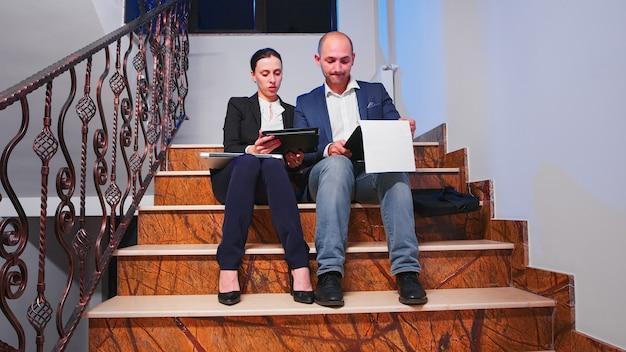 Trabajadores en equipo sentados en las escaleras en el edificio corporativo haciendo horas extraordinarias durante la fecha límite del proyecto financiero mirando tableta y documentos. emprendedores que trabajan juntos hasta tarde en trabajos corporativos.