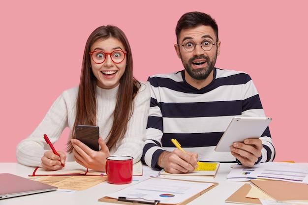 Los trabajadores del equipo se sientan en un escritorio, toman notas en el bloc de notas, se preparan para el seminario, sostienen un teléfono inteligente moderno y un panel táctil, tienen una mirada feliz, estudian documentos con gráficos, participan en el proceso de trabajo