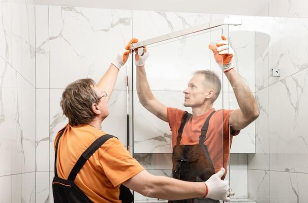 Los trabajadores están instalando la puerta de vidrio de la cabina de ducha.