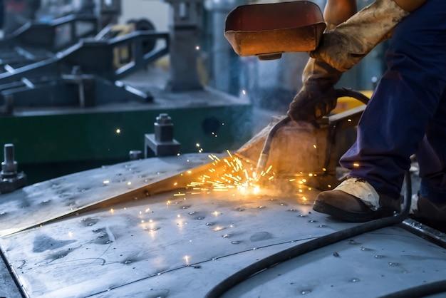 Los trabajadores están soldando piezas en el taller