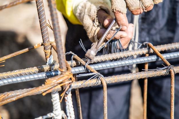 Los trabajadores están utilizando alambre y alicates para atar la barra de refuerzo utilizada para los cimientos de la construcción.