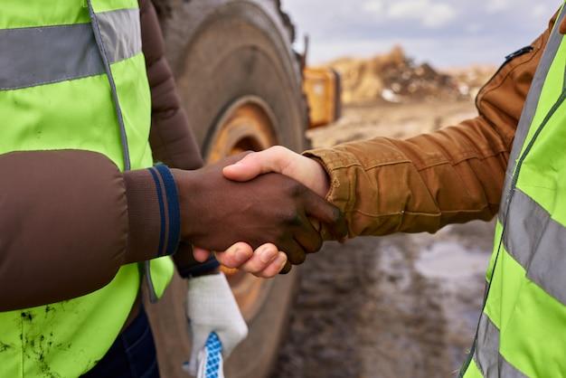 Trabajadores estrecharme la mano al aire libre closeup