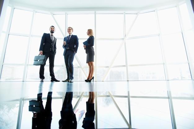 Trabajadores exitosos de pie en la sala