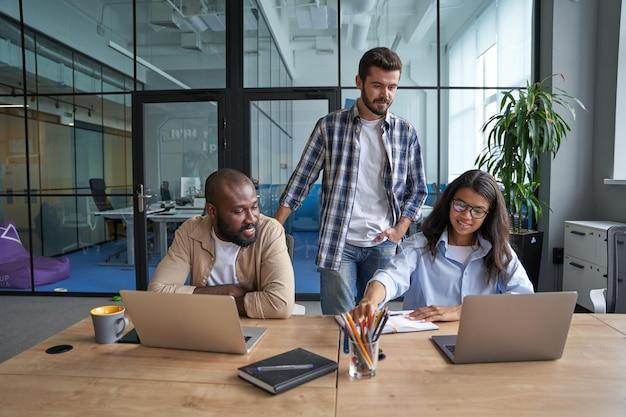 Trabajadores experimentados hablando sobre declaraciones juntos en la oficina