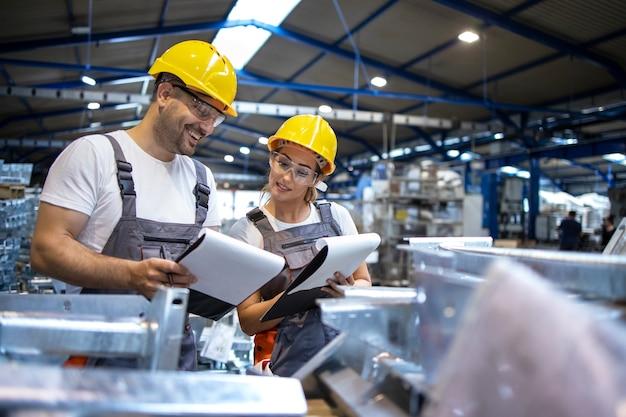 Trabajadores de la fábrica analizando los resultados de producción en una gran nave industrial