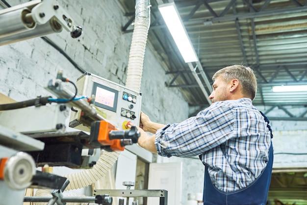 Trabajadores de fábrica maduros que operan máquinas