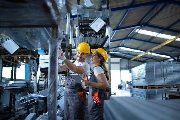 Trabajadores de la fábrica que controlan el inventario con la tableta en el almacén industrial lleno de piezas metálicas