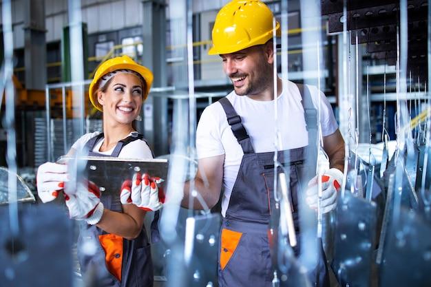 Trabajadores de la fábrica que trabajan juntos en la línea de producción de metales industriales