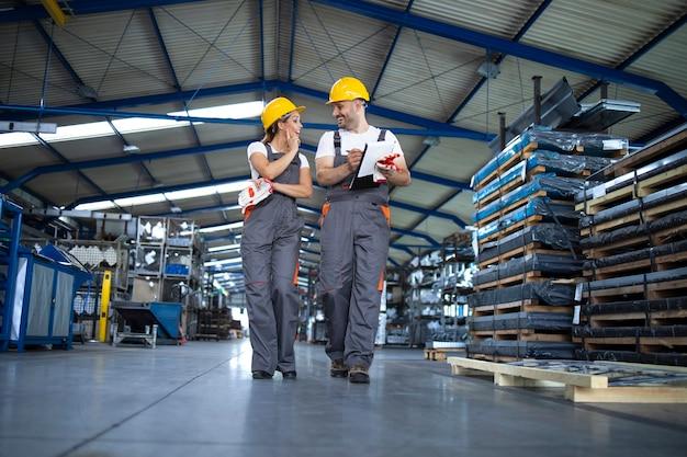 Trabajadores de la fábrica en ropa de trabajo y cascos amarillos caminando por la sala de producción industrial y discutiendo sobre la mejora de la eficiencia