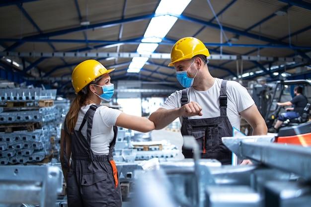 Los trabajadores de la fábrica se saludan con los codos durante la pandemia del virus corona